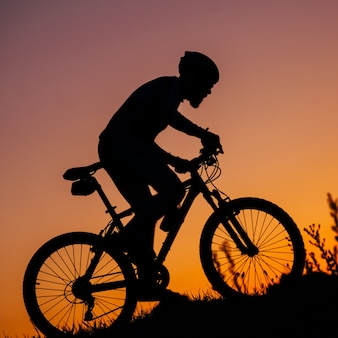 The young man riding a bike at sunset