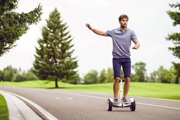 Young man riding a gyroboard along the way.