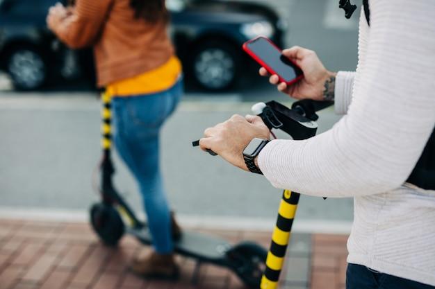 電動スクーターに乗って携帯電話を見ている青年。