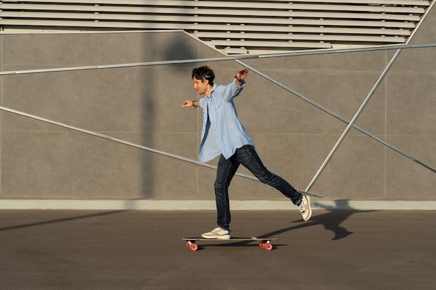 도시 거리 스케이트파크에서 롱보드를 타는 젊은 남자 캐주얼 힙스터 남자는 반다나 스케이트보드를 입는다