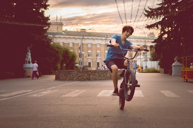 Молодой человек катается на велосипеде bmx на заднем заднем колесе, делает трюки в городе