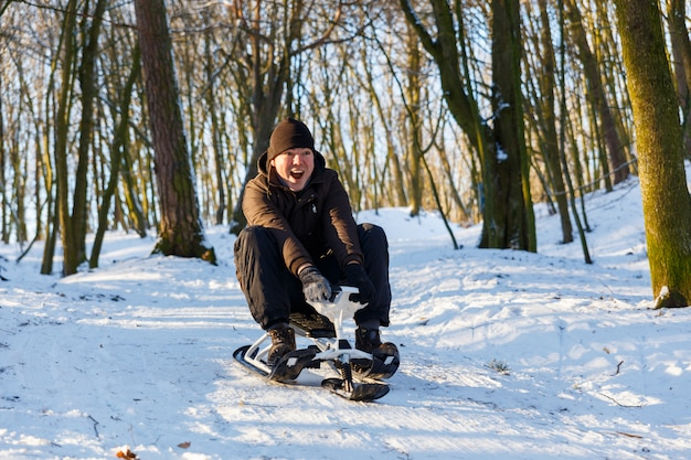Young man riding a snow scooter