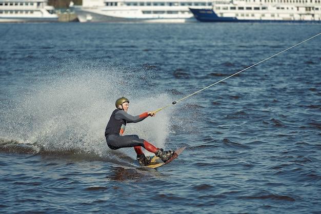 Молодой человек катается на вейкборде на летнем озере