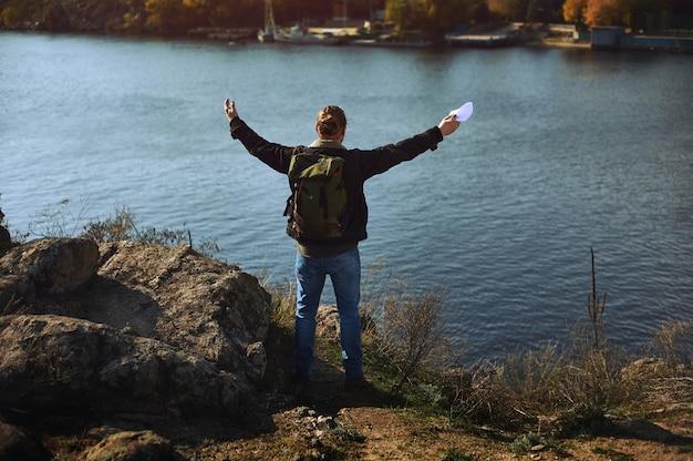젊은 남자는 아름 다운 호수와 산 풍경에 손을 상승. 두 팔을 벌려 산에 서서 아름다운 가을 풍경을 즐기는 남자.