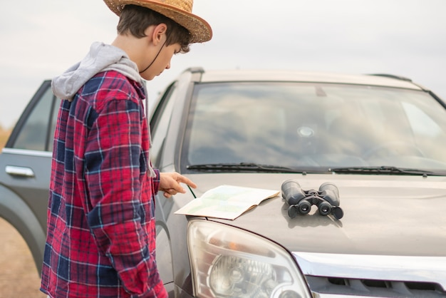 Young man on a road trip with car using binocular and search the way