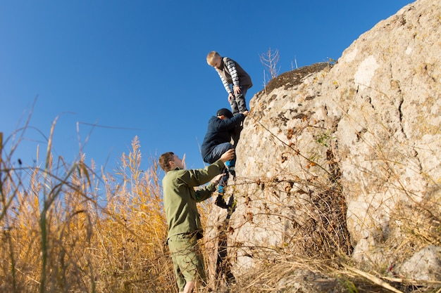 두 명의 작은 소년과 함께 암벽 등반을 하는 청년 암벽 등반은 맑고 맑은 푸른 하늘 아래 정상으로 가는 마지막 가파른 구간을 오르도록 도와줍니다.