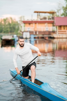 Young man rowing with paddle