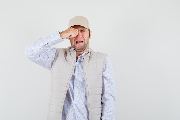Young man rubbing eye and crying in beige jacket and cap and looking lugubrious. front view.