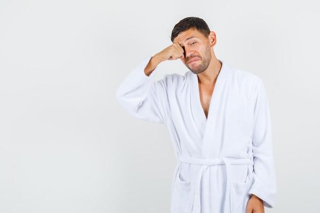 若い男は白いバスローブで目をこすり、動揺して、正面図を探しています。