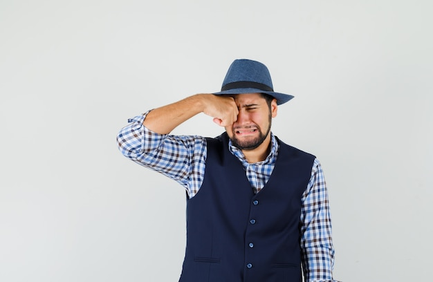 Young man rubbing eye while crying in shirt, vest, hat and looking offended.
