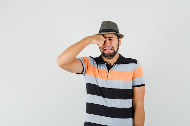 Young man rubbing eye while crying in t-shirt, hat and looking offended