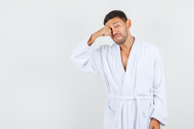 Young man rubbing eye in white bathrobe and looking upset , front view.