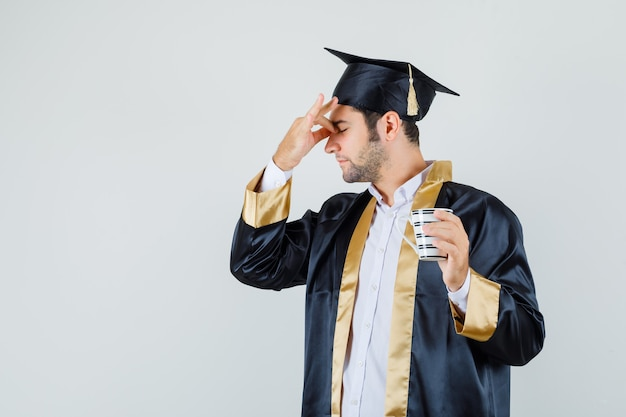 Young man rubbing eyes, holding cup of drink in graduate uniform and looking tired. front view.
