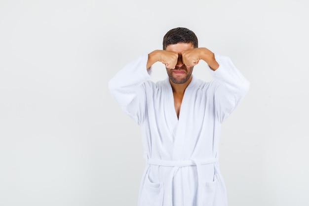 若い男は白いバスローブで目をこすり、動揺して見えます。正面図。
