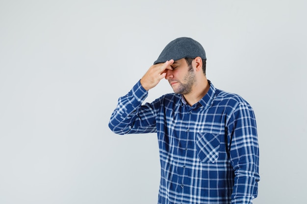 Young man rubbing eyes and nose in shirt, cap and looking tired. front view.
