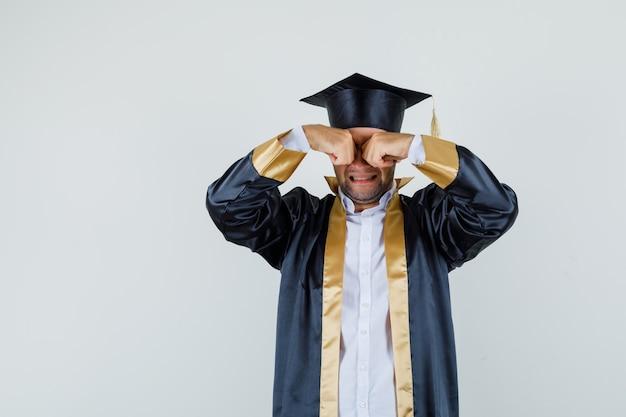 대학원 유니폼을 입고 우는 동안 눈을 문지르는 젊은 남자가 불쾌한 모습을 보입니다.