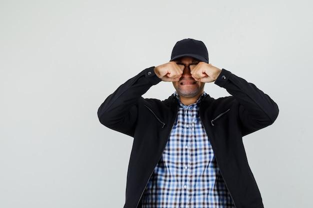 Молодой человек протирает глаза, плачет в рубашке, куртке, кепке и обиженно, вид спереди.