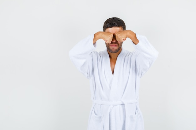 Young man rubbing eyes in white bathrobe and looking upset. front view.