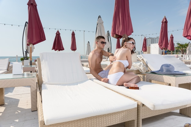 Young man rubbing sunscreen lotion onto back of young woman while relaxing together on lounge chair on sunny deck of luxury beachfront vacation resort
