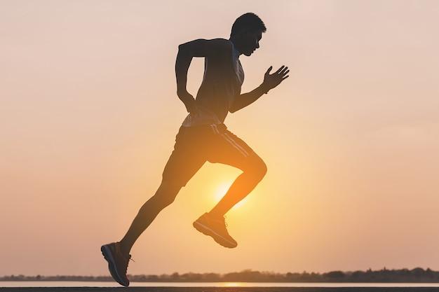 Молодой человек бегун на беговой дороге в городском парке