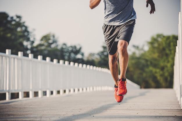 Young man runner running on running road in city park