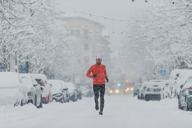 Young man runner under a snowfall in the city