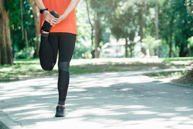 足を伸ばす若い男のランナー。アクティブで健康的なライフスタイルのコンセプト。