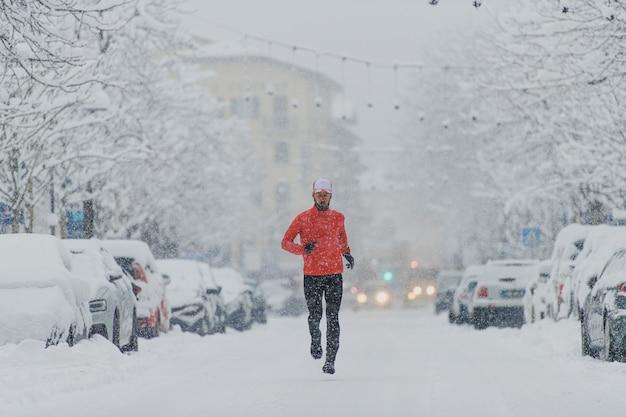 街の降雪の下で若い男のランナー
