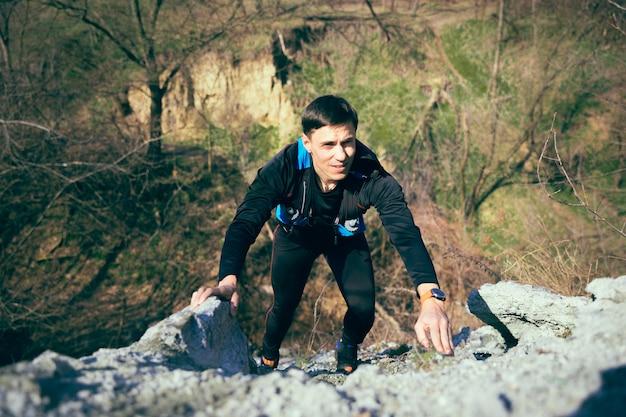 숲에서 실행하는 젊은 남자.