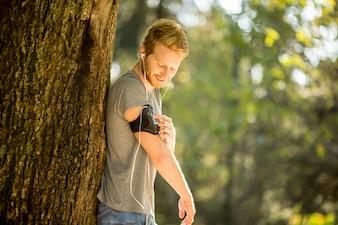 秋の公園で走っている若い男