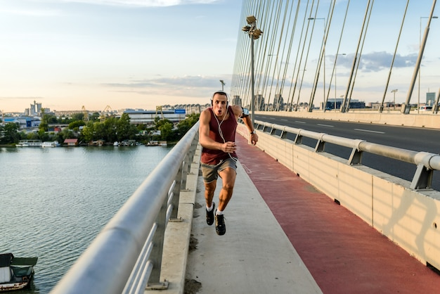 Young man running on the modern bridge in the city