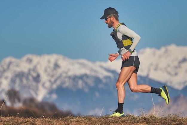 山の牧草地を走る青年