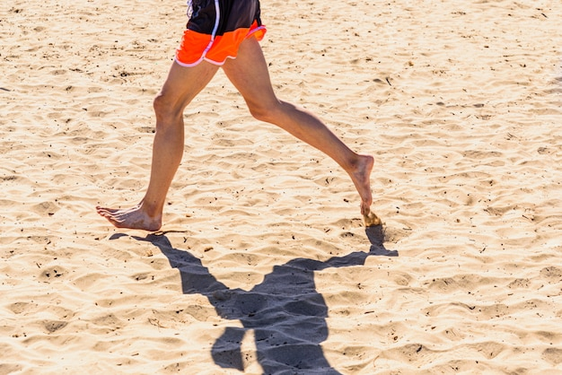 Young man running through the sand of a beach.