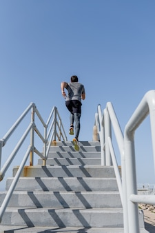 澄んだ空で二階を走っている若い男は、スポーツウェアを着ています