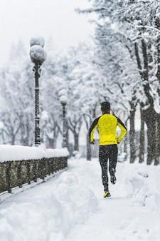 젊은 남자가 겨울에 눈 덮인 보도에서 실행
