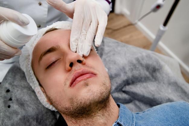 Молодой человек тщательно готовит кожу к чистке лица от прыщей. решает некоторые возрастные проблемы кожи и делает ее мягкой и здоровой.