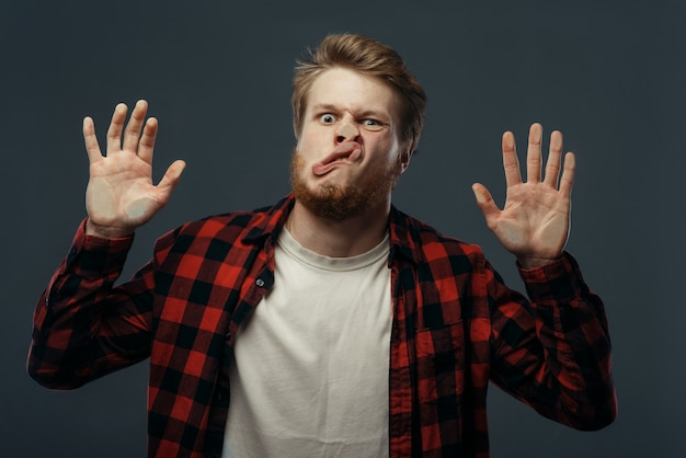 Young man's crazy face and hands crushed on transparent glass.