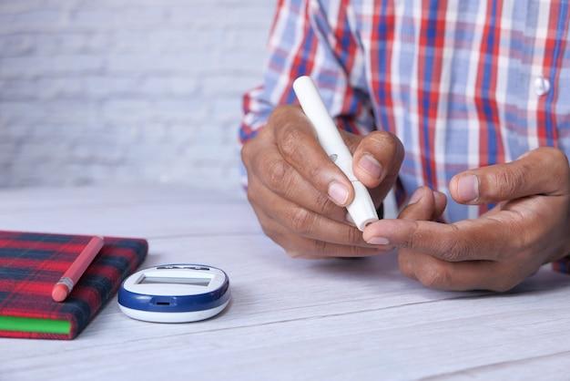 若い男の手は自宅でブドウ糖レベルを測定します
