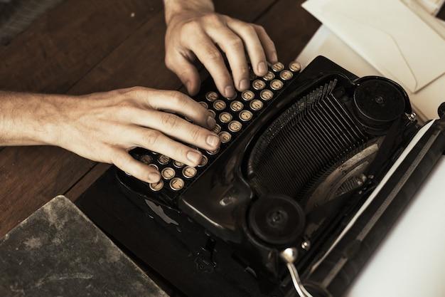 골동품 빈티지 타자기에 입력하는 젊은 남자의 손