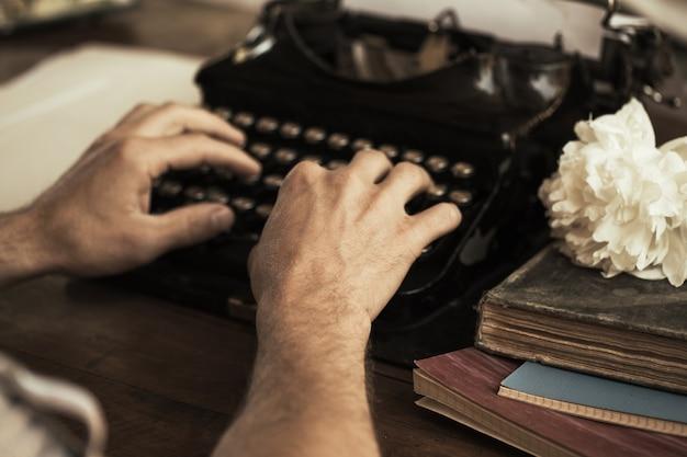 Руки молодого человека печатают на старинной старинной пишущей машинке
