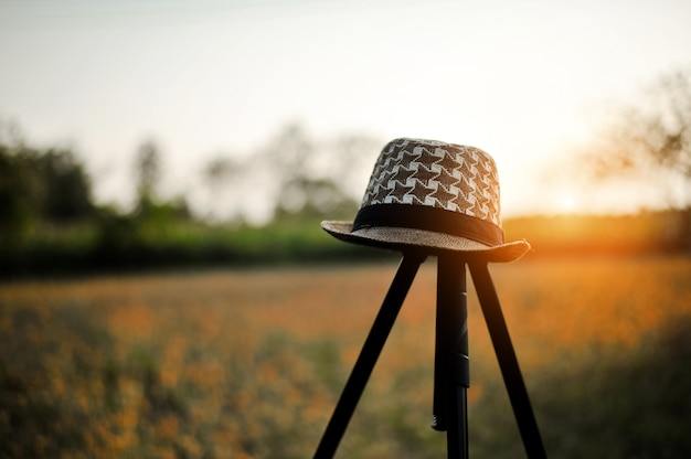 A young man's hat is placed on a tripod.