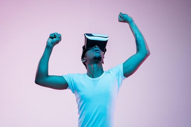 Молодой человек играет и использует vr-очки в неоновом свете на градиенте