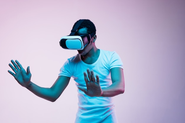 Young man's playing and using vr-glasses in neon light on gradient