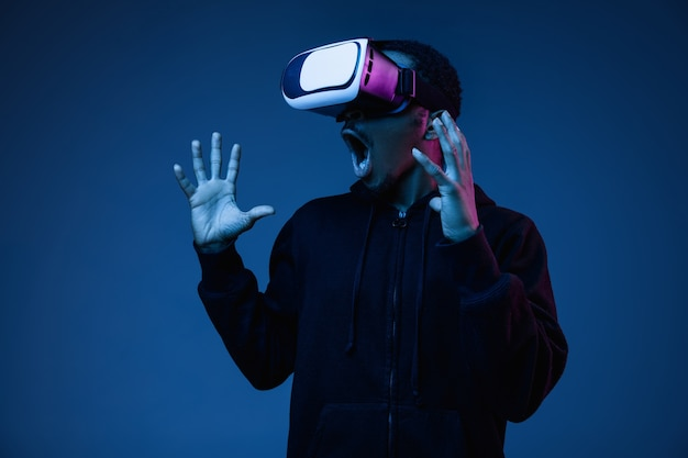 Young man's playing in vr-glasses in neon light