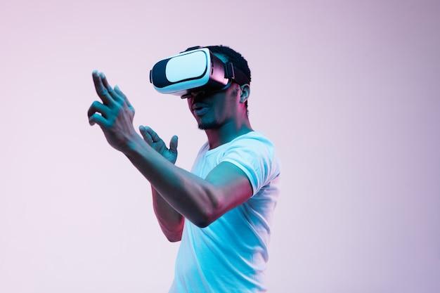 Молодой человек указывает и использует vr-очки в неоновом свете на градиенте