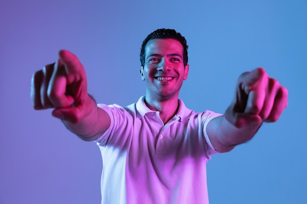Портрет молодого человека в неоновом свете. красивая мужская модель, указывая на фронт