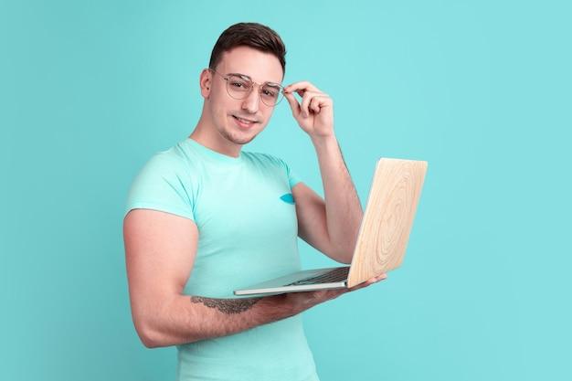 Портрет молодого человека, изолированные на синей стене студии