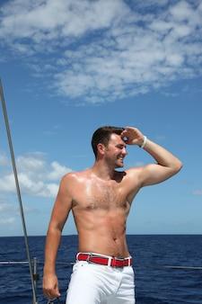 Молодой человек плывет на лодке в открытом океане
