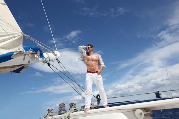 넓은 바다에서 그의 배를 항해하는 젊은 남자