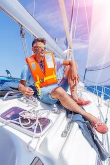 若い男セーリングヨットのハンドルの休暇の帆。休日、人、旅行